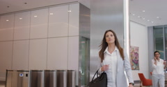 Attractive successful businesswoman leaving corporate office lobby checking Stock Footage