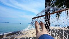 POV of Feet swinging in a hammock on coconut tree. Relaxing on the beach - stock footage