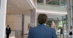 Mature businessman walking to work in busy corporate office lobby Stock Footage