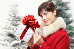 woman with Christmas gift box, looks ahead, with trees in the background - stock photo