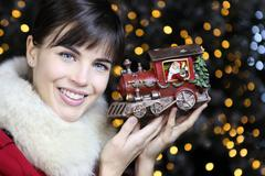Christmas woman smiling with train toy on lights background Stock Photos