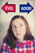 Portrait of beautiful teenage girl choosing between GOOD and EVIL - stock photo