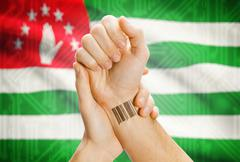 Barcode ID number on wrist of a human and national flag on background - Abkha - stock photo