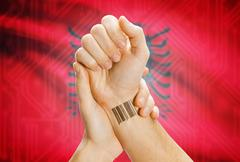 Barcode ID number on wrist of a human and national flag on background - Alban Stock Photos