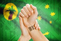 Barcode ID number on wrist of a human and national flag on background - Cocos - stock photo