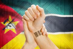 Stock Photo of Barcode ID number on wrist of a human and national flag on background - Mozam