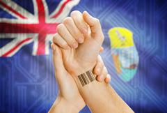 Barcode ID number on wrist of a human and national flag on background - Ascen - stock photo