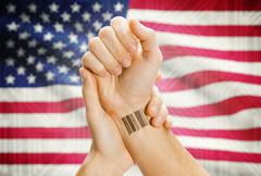 Barcode ID number on wrist of a human and national flag on background - Unite - stock photo