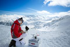 engineer with remote controls quadrocopter drone a the mountains - stock photo