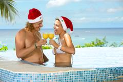 Couple in swimming pool toasting for Christmas Kuvituskuvat