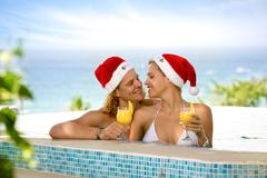 Lovers couple with Santa hats in swimming pool Kuvituskuvat