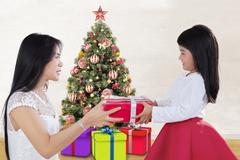 Child giving christmas gift on her mother - stock photo