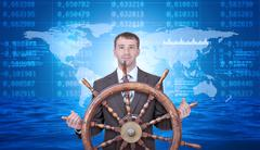 Smiling businessman with steering wheel and map - stock photo