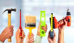 Hands of handyman with tools. Stock Photos