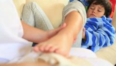Nurse bandaging little boy ankle 2 Stock Footage
