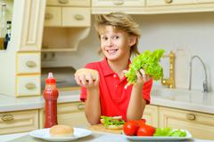 Smiling boy holding a hamburger bun and salad in the kitchen Stock Photos