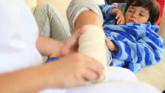 Nurse bandaging little boy ankle Stock Footage