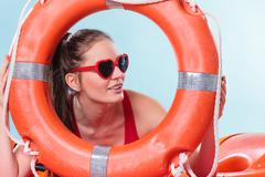 Stock Photo of Woman in sunglasses with ring buoy lifebuoy.