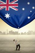 Man pulling Australian flag - stock photo