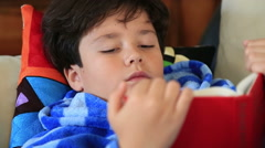Young boy lying on a couch and reading book 2 Stock Footage