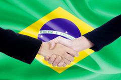 Two people shaking hands with Brazil flag backdrop Stock Photos