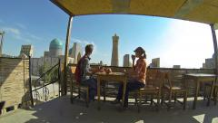 Couple of tourists sitting in a roof-teahouse in the old city of Bukhara Stock Footage