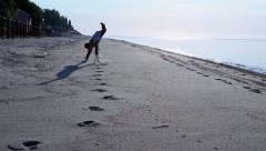 Man running and doing a cart wheel on sandy beach during sunrise Stock Footage