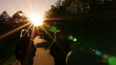 Stock Video Footage of Women couple on sunset autumn walk with stroller slow motion