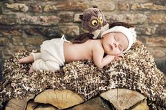 Newborn child sleeping on the wooden bed - stock photo