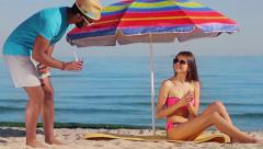 Macho flirting with a girl at the seaside. - stock footage