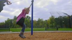 Two girls swing on swing set Stock Footage