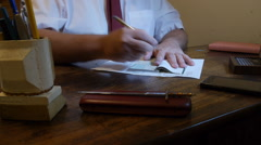 Man writing a check in his office desk Stock Footage