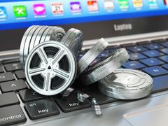 Stock Illustration of Video or movie online internet concept. Film reels on laptop keyboard.