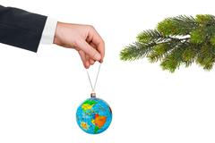 Hand with earth and Christmas tree Stock Photos