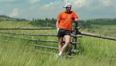 Man in orange t-shirt stands in field and communicate via smartphone Stock Footage