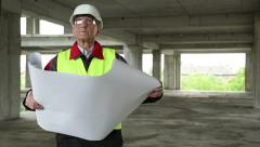Master builder with design drawings at construction site Stock Footage
