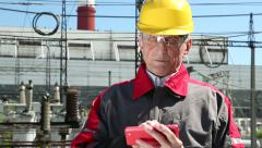 Maintenance worker with red smartphone at power station Stock Footage