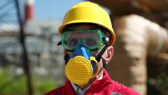 Repairman in hard hat, goggles and respirator at industrial area - stock footage