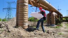 Maintenance engineer with design drawings at heat station Stock Footage