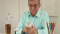 Stock Video Footage of Senior man with white mobile phone and bottle of cognac sits at a table