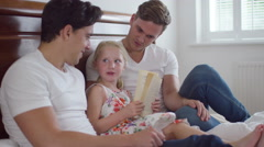 4K Gay male couple relaxing at home & reading with daughter Stock Footage