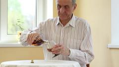 Senior man sits at the table and pours brandy in glass Stock Footage