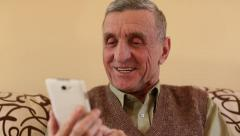 Senior man looking and flipping through the photos in her smartphone Stock Footage
