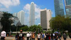 HONG KONG - People crossing street in city centre with skyscrapers in background Stock Footage