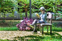 Alloy Children reading book on chair in home garden. - stock photo