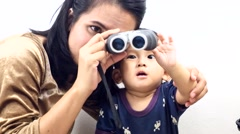 Young Mother with a Child looking through binoculars in room Stock Footage