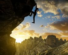 Silhoutte of girl climbing on rock at sunset in Sexten Dolomites - stock photo