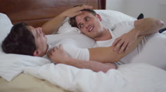 4K Affectionate young gay couple relaxing & chatting in bed Stock Footage
