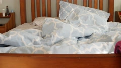 A man getting in to bed during the day Stock Footage