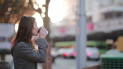 Beautiful woman drinking coffee on the street Stock Footage